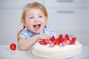 Kind feiert Geburtstag mit einem frischen Erdbeerkuchen