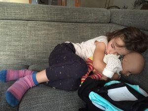 Kleines Mdchen schlft mit ihrer Puppe auf dem Sofa