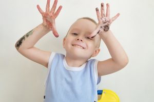 Little boy covered in paint naughty and waving hands. Mischievous child.
