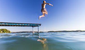 Junge springt vom Steg in den See