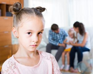 Little girl sad because of jealous younger sister to parents. focus on girl